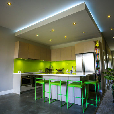 Example of a small trendy l-shaped concrete floor eat-in kitchen design in Sydney with flat-panel cabinets, light wood cabinets, green backsplash, stainless steel appliances, an undermount sink, solid surface countertops, glass sheet backsplash and an island