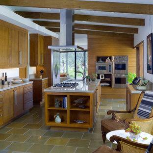 Idée de décoration pour une cuisine design avec un placard à porte shaker, des portes de placard en bois brun, une crédence grise et un électroménager en acier inoxydable.