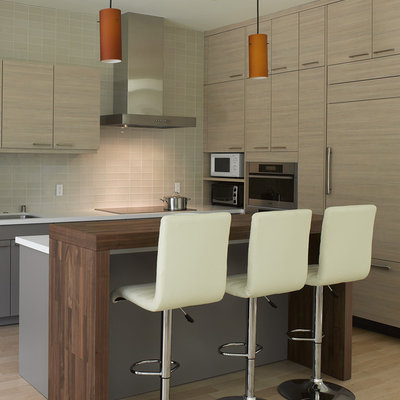Example of a small minimalist l-shaped light wood floor and beige floor eat-in kitchen design in San Francisco with wood countertops, flat-panel cabinets, paneled appliances, light wood cabinets, beige backsplash, glass tile backsplash and an island