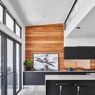 Bild på ett mellanstort funkis vit vitt kök, med en undermonterad diskho, svarta skåp, bänkskiva i betong, stänkskydd i trä, rostfria vitvaror, betonggolv, en köksö och grönt golv