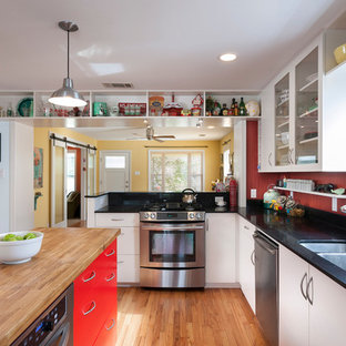 Large transitional l-shaped eat-in kitchen in Austin with a double-bowl sink, glass-front cabinets, white cabinets, stainless steel appliances, quartz benchtops, red splashback, light hardwood floors and multiple islands.
