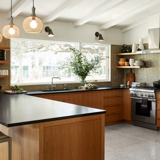 Mid-sized mid-century modern eat-in kitchen remodeling - Inspiration for a mid-sized mid-century modern u-shaped terrazzo floor and white floor eat-in kitchen remodel in Austin with a drop-in sink, flat-panel cabinets, brown cabinets, green backsplash, stainless steel appliances, no island and black countertops