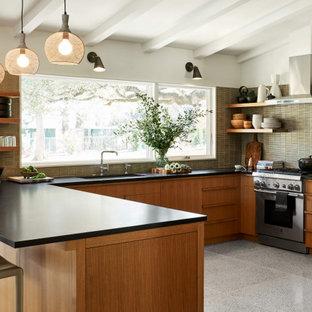 Inredning av ett retro mellanstort svart svart kök, med en nedsänkt diskho, släta luckor, bruna skåp, grönt stänkskydd, rostfria vitvaror, terrazzogolv och vitt golv