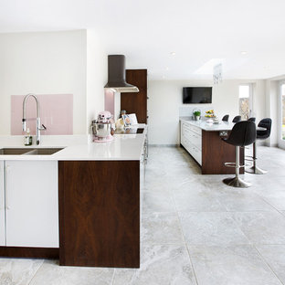 Huge contemporary eat-in kitchen pictures - Inspiration for a huge contemporary ceramic floor and gray floor eat-in kitchen remodel in West Midlands with a double-bowl sink, flat-panel cabinets, white cabinets, quartzite countertops, pink backsplash, glass sheet backsplash, stainless steel appliances and an island