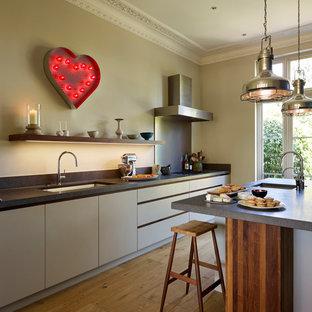 Offene, Einzeilige, Große Moderne Küche mit integriertem Waschbecken, flächenbündigen Schrankfronten, weißen Schränken, Kalkstein-Arbeitsplatte, hellem Holzboden, Kücheninsel, braunem Boden und schwarzer Arbeitsplatte in London