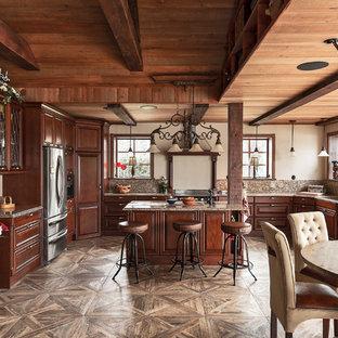 Inredning av ett rustikt kök, med en undermonterad diskho, luckor med upphöjd panel, skåp i mörkt trä, rostfria vitvaror, en köksö och brunt golv
