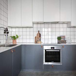 Idéer för minimalistiska vitt u-kök, med en enkel diskho, släta luckor, grå skåp, vitt stänkskydd, rostfria vitvaror, betonggolv och grått golv