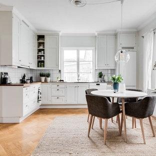 Idéer för att renovera ett avskilt skandinaviskt l-kök, med luckor med infälld panel, vita skåp, träbänkskiva, vitt stänkskydd, vita vitvaror, ljust trägolv och beiget golv