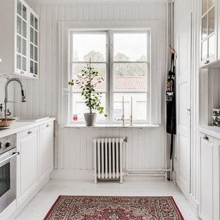 Bild på ett mellanstort lantligt parallellkök, med luckor med glaspanel, vitt stänkskydd, rostfria vitvaror, vitt golv och vita skåp