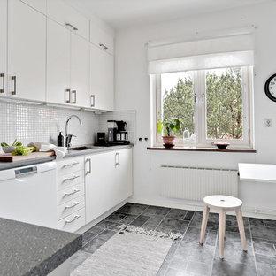 Minimalistisk inredning av ett kök och matrum, med släta luckor, vita skåp, vitt stänkskydd, laminatgolv, grått golv och vita vitvaror
