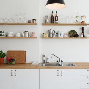 Diseño de cocina lineal, escandinava, de tamaño medio, sin isla, con puertas de armario blancas, electrodomésticos de acero inoxidable, fregadero de doble seno, armarios con paneles lisos y encimera de madera