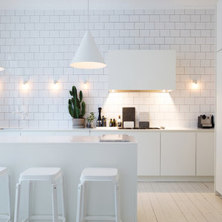Einzeilige, Mittelgroße Nordische Wohnküche mit flächenbündigen Schrankfronten, weißen Schränken, Küchenrückwand in Weiß, Rückwand aus Metrofliesen, gebeiztem Holzboden, Kücheninsel, Marmor-Arbeitsplatte und weißen Elektrogeräten in Stockholm