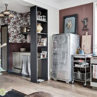 Idéer för att renovera ett litet eklektiskt linjärt kök med öppen planlösning, med rostfria vitvaror, ljust trägolv och beiget golv