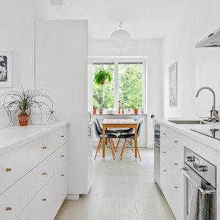 Foto på ett skandinaviskt kök, med en nedsänkt diskho, släta luckor, vita skåp, spegel som stänkskydd, rostfria vitvaror, en halv köksö och beiget golv
