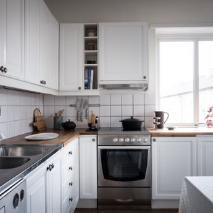Idéer för ett mellanstort skandinaviskt beige l-kök, med en dubbel diskho, luckor med upphöjd panel, vita skåp, träbänkskiva, vitt stänkskydd, stänkskydd i porslinskakel och rostfria vitvaror