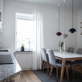 Idéer för skandinaviska grått kök, med en undermonterad diskho, släta luckor, vita skåp, vitt stänkskydd, stänkskydd i mosaik, svarta vitvaror, ljust trägolv och beiget golv