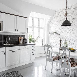 Inredning av ett minimalistiskt mellanstort kök, med en undermonterad diskho, skåp i shakerstil, vita skåp, svart stänkskydd, rostfria vitvaror och betonggolv