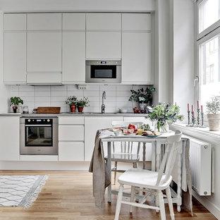 Foto på ett mellanstort skandinaviskt linjärt kök och matrum, med släta luckor, vita skåp, vitt stänkskydd, rostfria vitvaror och ljust trägolv