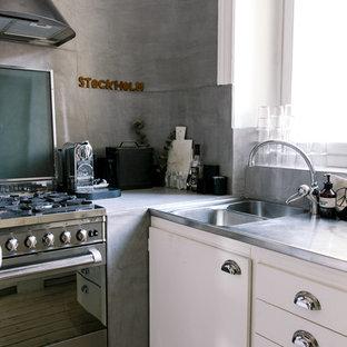 Diseño de cocina en L, industrial, pequeña, cerrada, sin isla, con fregadero de doble seno, puertas de armario blancas, encimera de acero inoxidable, electrodomésticos de acero inoxidable, suelo de madera clara y armarios con paneles con relieve