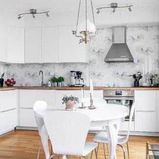 Idéer för ett litet skandinaviskt brun kök, med släta luckor, vita skåp, träbänkskiva, rostfria vitvaror, mellanmörkt trägolv och brunt golv