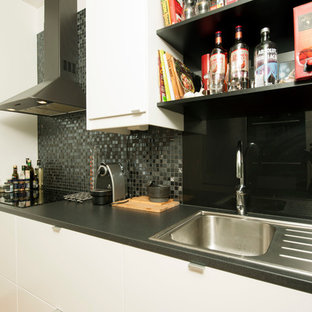 Small contemporary enclosed kitchen ideas - Inspiration for a small contemporary single-wall enclosed kitchen remodel in Stockholm with white cabinets and black appliances