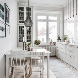 Idéer för minimalistiska kök, med marmorbänkskiva, vitt stänkskydd, rostfria vitvaror, ljust trägolv, beiget golv, skåp i shakerstil, vita skåp och stänkskydd i tunnelbanekakel