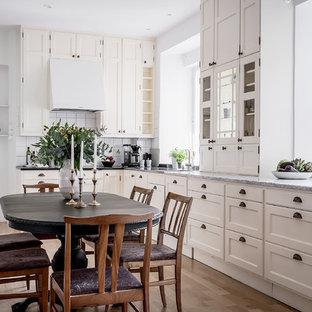 Inspiration för klassiska kök, med vitt stänkskydd, mellanmörkt trägolv, skåp i shakerstil och beige skåp