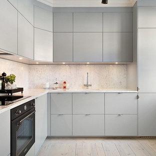 Idéer för att renovera ett mellanstort skandinaviskt l-kök, med en enkel diskho, släta luckor, grå skåp, vitt stänkskydd, svarta vitvaror och ljust trägolv