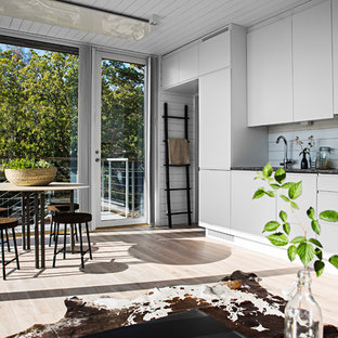 Inspiration for a mid-sized scandinavian galley open plan kitchen in Stockholm with a drop-in sink, flat-panel cabinets, white cabinets, limestone benchtops, white splashback, glass sheet splashback, white appliances and light hardwood floors.
