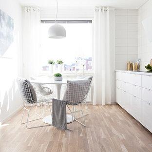 Foto på ett skandinaviskt vit kök, med släta luckor, vita skåp, vitt stänkskydd, ljust trägolv och beiget golv