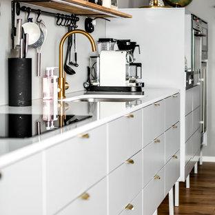 Foto på ett mellanstort skandinaviskt linjärt kök, med en enkel diskho, släta luckor, grå skåp och mellanmörkt trägolv
