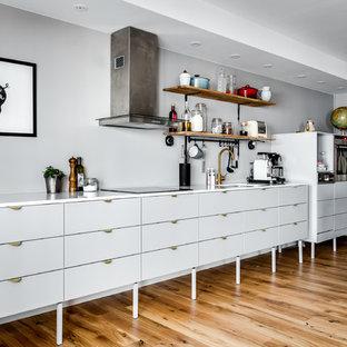 Exempel på ett mellanstort industriellt linjärt kök med öppen planlösning, med släta luckor, grå skåp, grått stänkskydd, rostfria vitvaror, mellanmörkt trägolv och en köksö