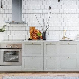 ストックホルムの大きい北欧スタイルのおしゃれなI型キッチン (アンダーカウンターシンク、シェーカースタイル扉のキャビネット、グレーのキャビネット、白いキッチンパネル、サブウェイタイルのキッチンパネル、シルバーの調理設備の、淡色無垢フローリング、アイランドなし) の写真
