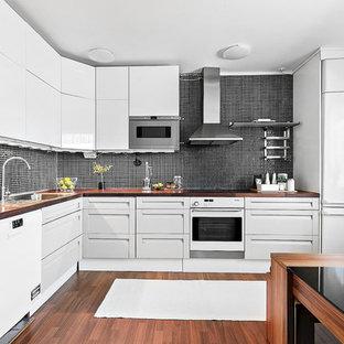 Idéer för minimalistiska l-kök, med släta luckor, vita skåp, svart stänkskydd, vita vitvaror och ljust trägolv