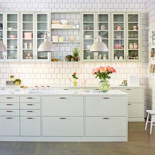 Exempel på ett skandinaviskt parallellkök, med släta luckor, gröna skåp, vitt stänkskydd, betonggolv och en köksö