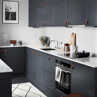 Bild på ett mellanstort funkis l-kök, med en köksö, en undermonterad diskho, släta luckor, vitt stänkskydd, svarta vitvaror, marmorbänkskiva och grå skåp