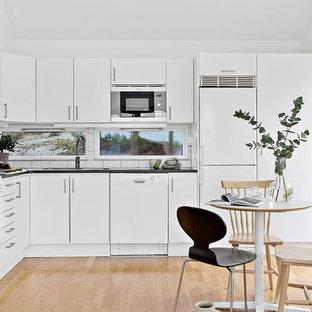 Idéer för minimalistiska svart kök, med en undermonterad diskho, släta luckor, vita skåp, vitt stänkskydd, stänkskydd i tunnelbanekakel, vita vitvaror, ljust trägolv och beiget golv