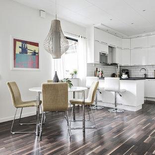 Exempel på ett litet nordiskt kök, med släta luckor, vita skåp, en halv köksö, brunt golv, vitt stänkskydd, stänkskydd i tunnelbanekakel och mörkt trägolv