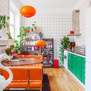 Einzeilige, Mittelgroße Eklektische Wohnküche ohne Insel mit profilierten Schrankfronten, grünen Schränken, Küchenrückwand in Weiß, weißen Elektrogeräten, braunem Holzboden und Edelstahl-Arbeitsplatte in Stockholm