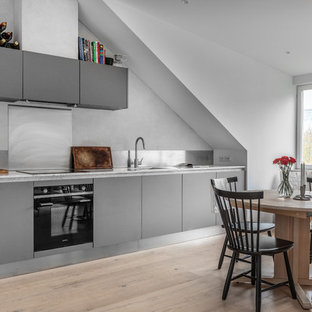 Idéer för att renovera ett skandinaviskt vit linjärt vitt kök och matrum, med en undermonterad diskho, släta luckor, grå skåp, marmorbänkskiva, stänkskydd med metallisk yta, svarta vitvaror och ljust trägolv
