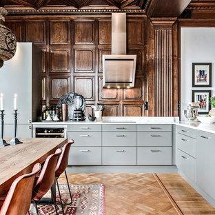 Idéer för nordiska vitt kök, med en undermonterad diskho, släta luckor, grå skåp, integrerade vitvaror, ljust trägolv och beiget golv