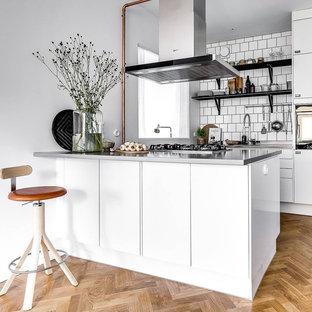 Foto på ett litet minimalistiskt kök, med en undermonterad diskho, släta luckor, vita skåp, vitt stänkskydd, svarta vitvaror, ljust trägolv, en halv köksö och beiget golv