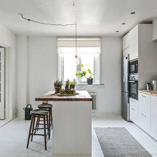 Idéer för avskilda minimalistiska brunt parallellkök, med släta luckor, vita skåp, träbänkskiva, vitt stänkskydd, rostfria vitvaror, målat trägolv, en köksö och vitt golv