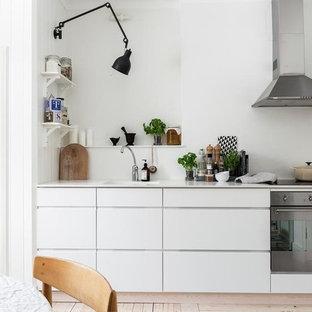 Bild på ett mellanstort skandinaviskt linjärt kök och matrum, med släta luckor, vita skåp, rostfria vitvaror, ljust trägolv och vitt stänkskydd