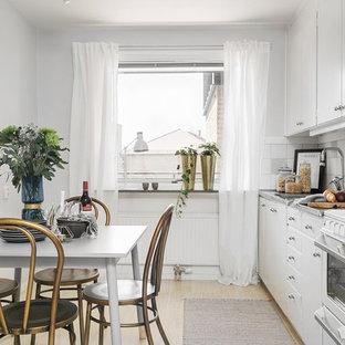 Foto på ett nordiskt linjärt kök och matrum, med släta luckor, vita skåp, vitt stänkskydd, ljust trägolv och beiget golv