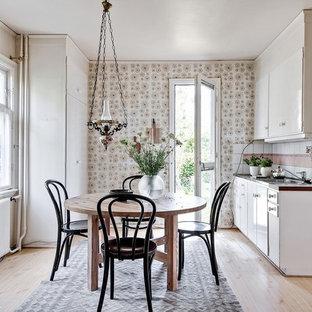 Idéer för att renovera ett skandinaviskt parallellkök, med släta luckor, vita skåp, vitt stänkskydd, vita vitvaror, ljust trägolv och beiget golv