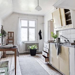 Bild på ett skandinaviskt grå linjärt grått kök och matrum, med en integrerad diskho, släta luckor, vita skåp, bänkskiva i rostfritt stål, vitt stänkskydd, vita vitvaror, ljust trägolv och beiget golv
