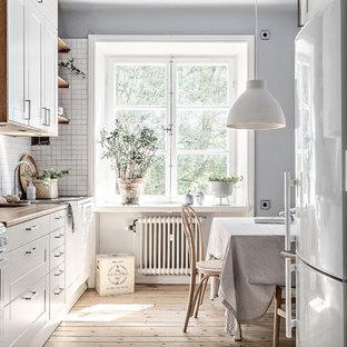 Inredning av ett minimalistiskt mellanstort beige beige kök och matrum, med vita skåp, träbänkskiva, vita vitvaror, ljust trägolv, beiget golv, en undermonterad diskho, vitt stänkskydd och skåp i shakerstil