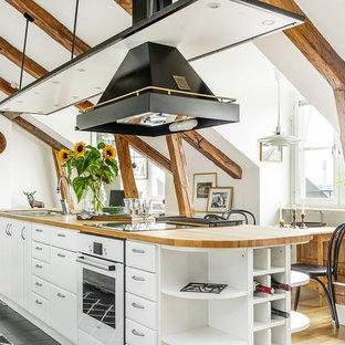 Idéer för ett mellanstort rustikt linjärt kök och matrum, med en nedsänkt diskho, öppna hyllor, vita skåp, träbänkskiva, vitt stänkskydd, rostfria vitvaror, ljust trägolv och en köksö