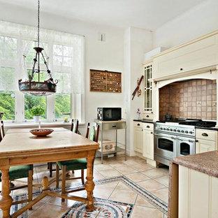 Inspiration för mellanstora lantliga kök, med luckor med infälld panel, gula skåp, träbänkskiva, brunt stänkskydd, stänkskydd i keramik, rostfria vitvaror och klinkergolv i keramik